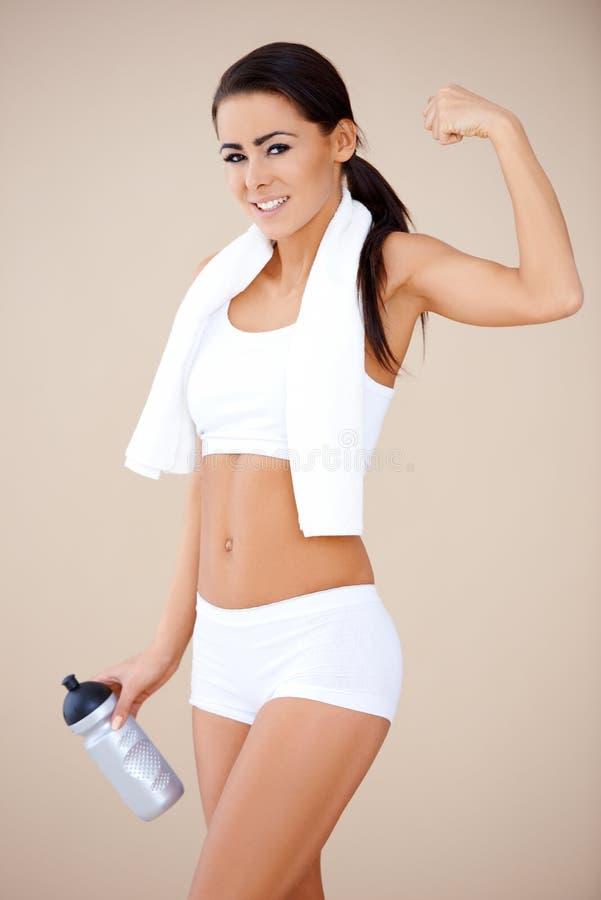Lycklig konditionflickavisning henne muskler royaltyfri foto