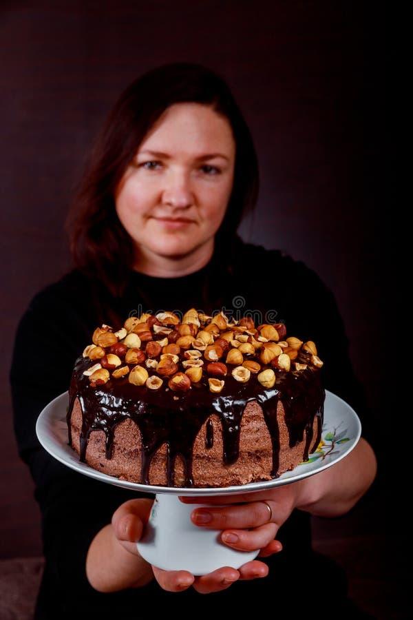 Lycklig konditor som visar hennes hemlagade kaka i hennes hand royaltyfria foton