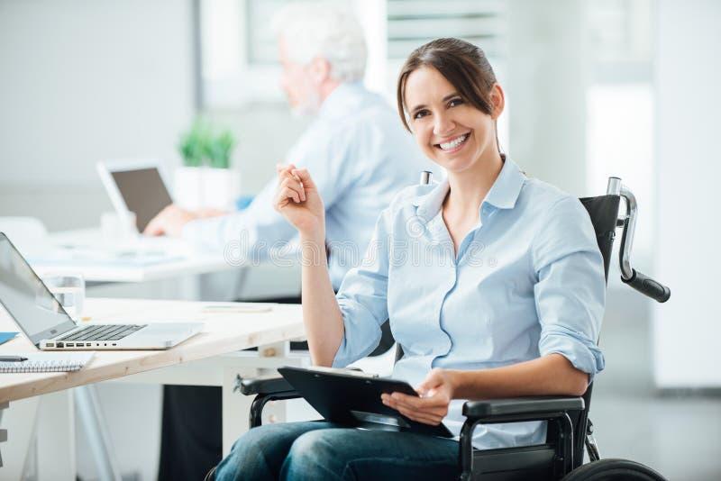 Lycklig kontorsarbetare i rullstol royaltyfria bilder