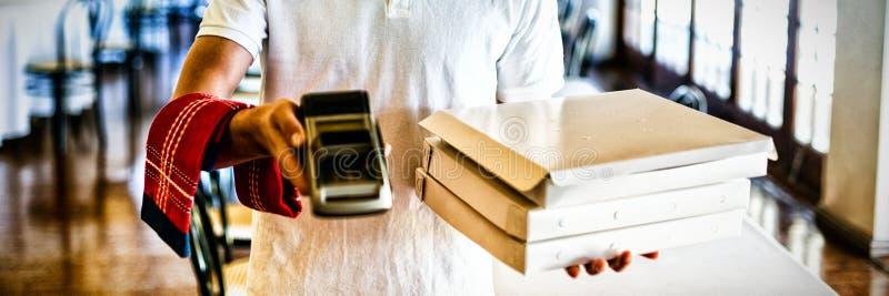 Lycklig kortläsare för visning för pizzaleveransman royaltyfria bilder