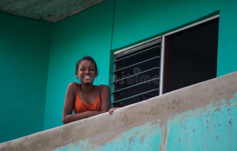 Lycklig kubansk flickastående i fattig färgrik kolonial gatagränd med leende och den vänliga framsidan, i gammal havannacigarr, K arkivbilder