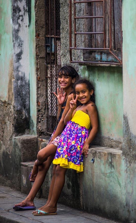 Lycklig kubansk flickatillfångatagandestående i fattig färgrik kolonial gränd med leendeframsidan, i gammal havannacigarr, Kuba,  arkivfoto