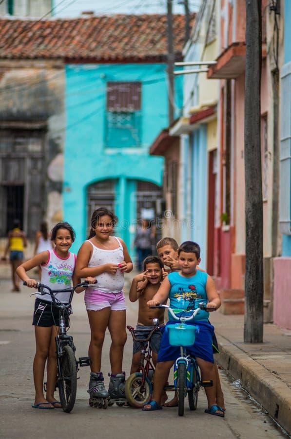 Lycklig kubansk pojke- och flickatillfångatagandestående i fattig färgrik kolonial gränd med leendeframsidan, i Camaguey, Kuba, A royaltyfri fotografi