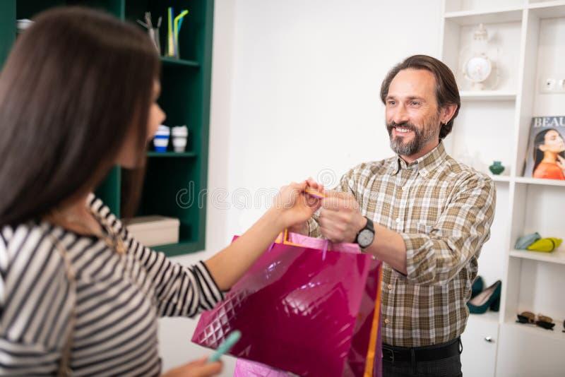 Lycklig kund som räcker de shoppa packarna till en kvinna arkivbild