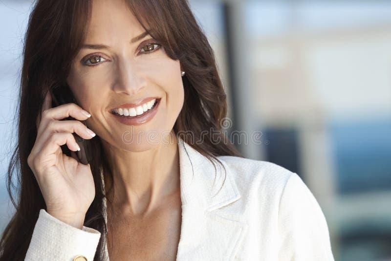 Lycklig kvinna eller affärskvinna som talar på celltelefonen royaltyfri foto