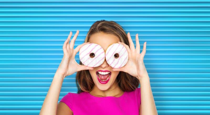 Lycklig kvinna eller tonårig flicka som ser till och med donuts arkivfoto
