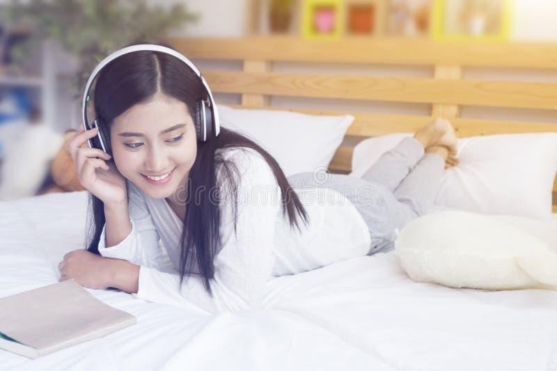 Lycklig kvinna eller tonårs- flicka i hörlurar som lyssnar till musik från smartphonen och som läser en bok på säng royaltyfri bild