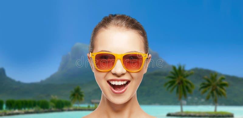 Lycklig kvinna eller tonårs- flicka i solglasögon på stranden fotografering för bildbyråer