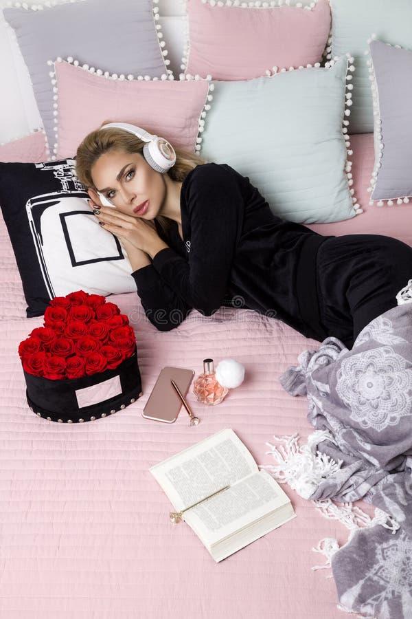 Lycklig kvinna eller tonårs- flicka med hörlurar som lyssnar till musik från smartphonen - bild Härlig flicka i pajamaen som ligg fotografering för bildbyråer