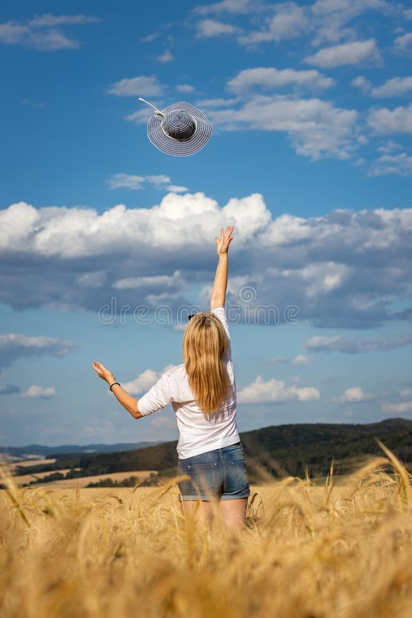 Lycklig kvinna för blont hår som kastar den blåa solhatten mot härlig himmel royaltyfria foton