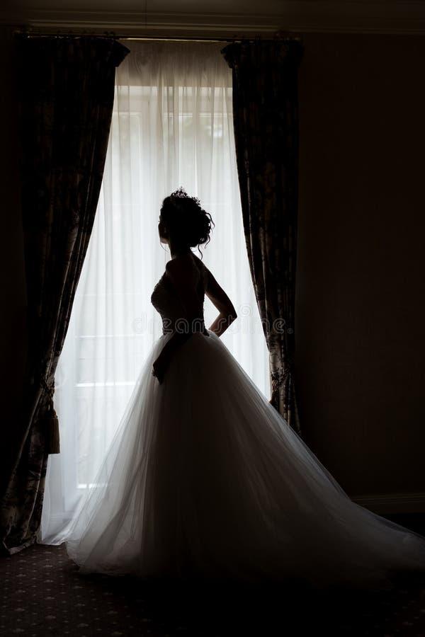 Lycklig kvinna för härlig delikat sexig brud med en krona på hennes huvud vid fönstret med en stor bröllopbukett i en lyxig vit arkivbild