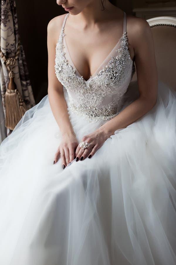 Lycklig kvinna för härlig delikat sexig brud med en krona på hennes huvud vid fönstret med en stor bröllopbukett i en lyxig vit royaltyfri bild