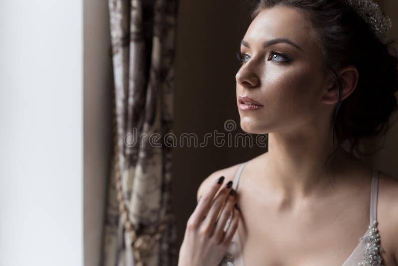 Lycklig kvinna för härlig delikat sexig brud med en krona på hennes huvud vid fönstret med en stor bröllopbukett i en lyxig vit fotografering för bildbyråer