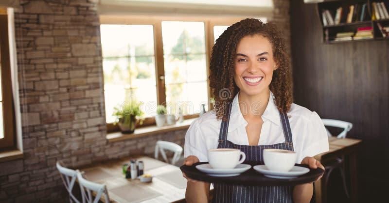 Lycklig kvinna för små och medelstora företagägare som rymmer två kaffe arkivbild
