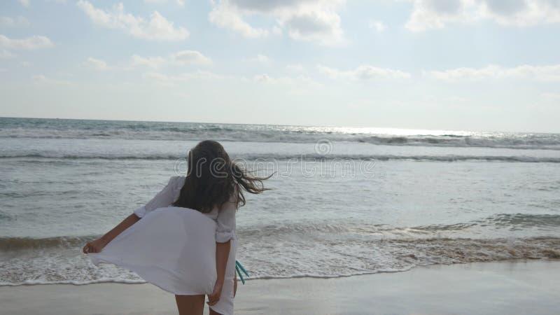 Lycklig kvinna i bikini och skjorta som går på stranden på havvattnet Ung härlig flicka som tycker om liv och har arkivfoto