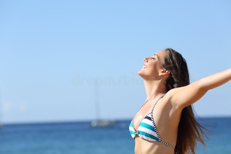 Lycklig kvinna i bikini som andas på stranden royaltyfria bilder