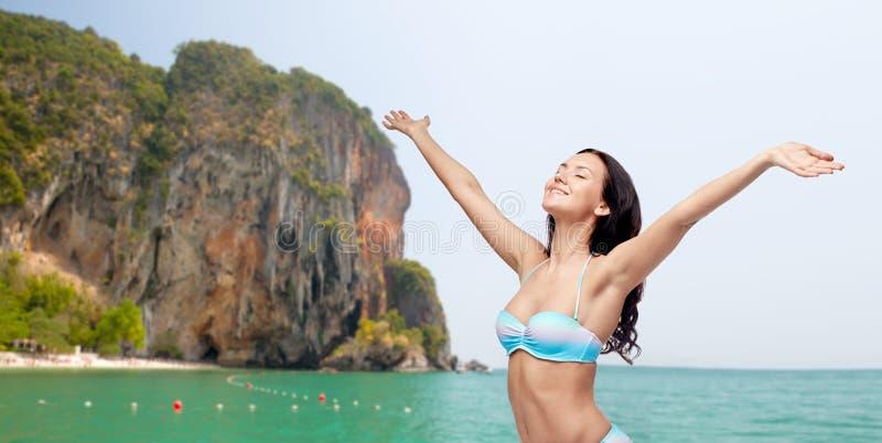 Lycklig kvinna i bikinibaddräkt med lyftta händer royaltyfria foton