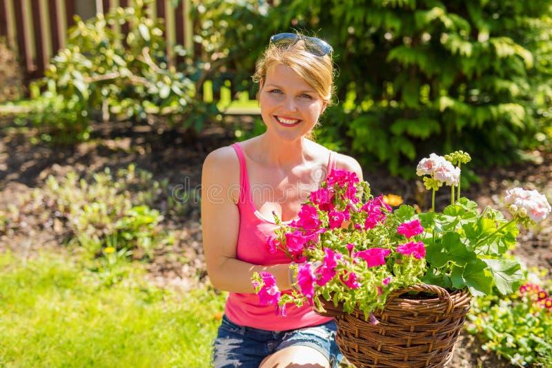 Lycklig kvinna i blommaträdgård royaltyfria foton