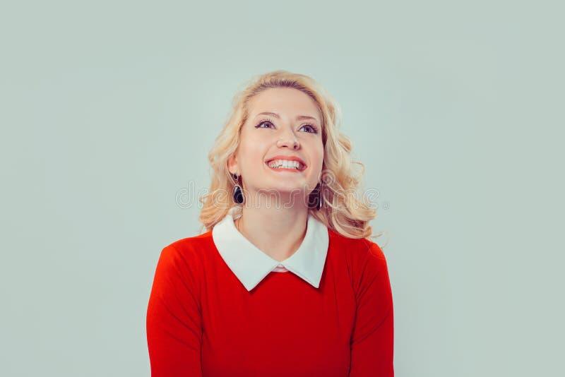 Lycklig kvinna i den röda klänningen som ser upp arkivfoton