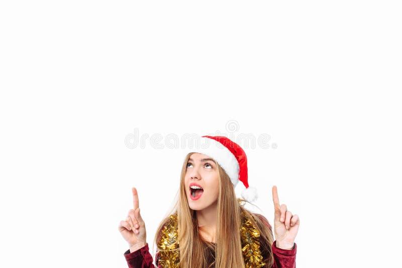 Lycklig kvinna i den santa hatten och klänningen som firar nytt år, lookin royaltyfria foton