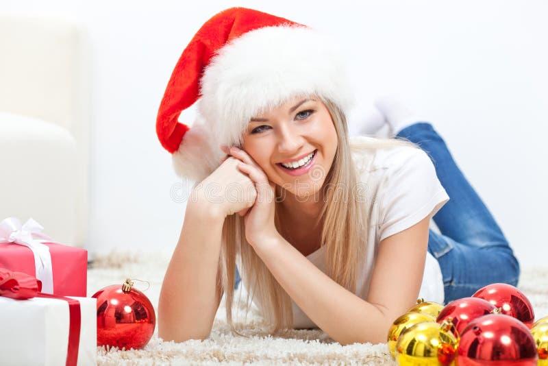 Lycklig kvinna i den santa hatten som lägger på matta arkivbild
