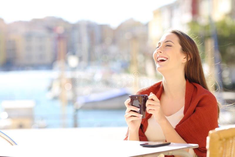 Lycklig kvinna i en coffee shop som tycker om fri tid arkivfoto