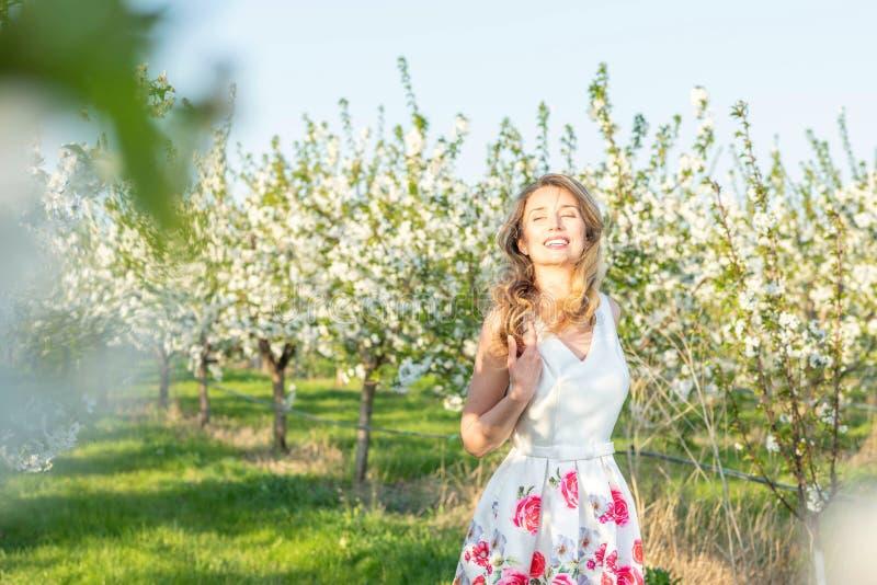 Lycklig kvinna i en fruktträdgård på vår Tycka om solig varm dag Retro stilkl?nning Blomma körsbärsröda träd för blomning royaltyfria foton