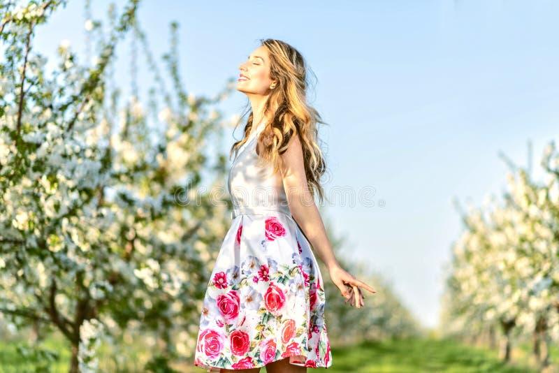 Lycklig kvinna i en fruktträdgård på vår Tycka om solig varm dag Retro stilkl?nning Blomma körsbärsröda träd för blomning arkivfoto