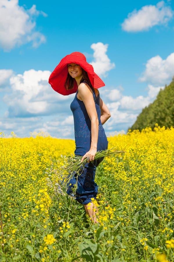 Lycklig kvinna i en röd hatt med en bukett av vildblommor royaltyfria foton