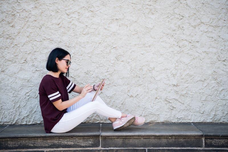 Lycklig kvinna i exponeringsglas genom att använda minnestavlaPC i gatan arkivfoton