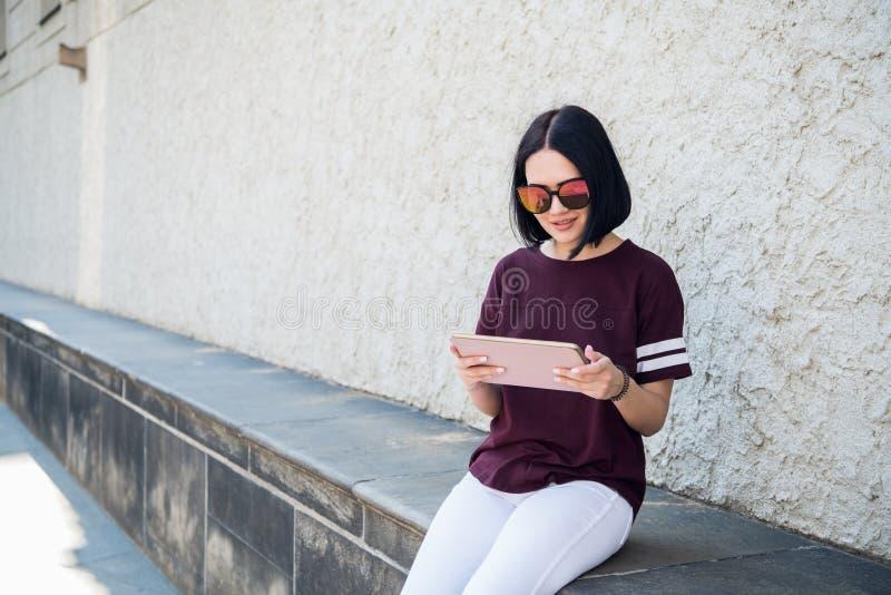 Lycklig kvinna i exponeringsglas genom att använda minnestavlaPC i gatan royaltyfri fotografi