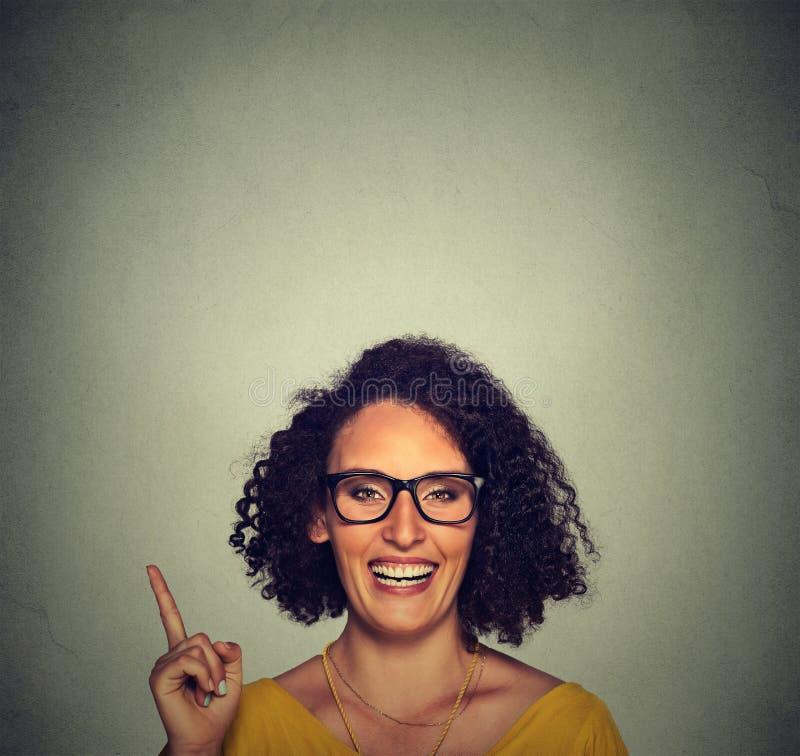 Lycklig kvinna i exponeringsglas som pekar upp med hennes finger royaltyfri bild