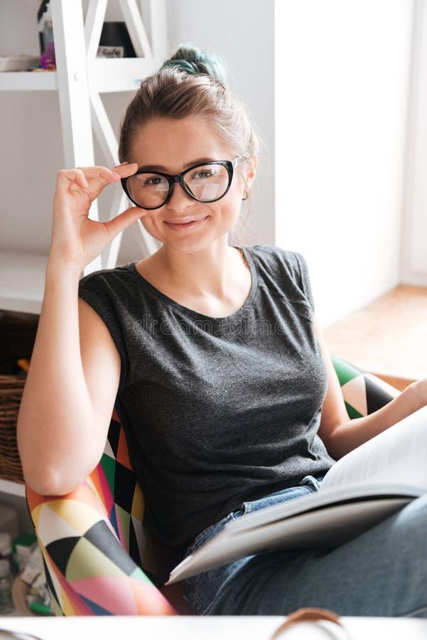 Lycklig kvinna i exponeringsglasläsebok hemma fotografering för bildbyråer