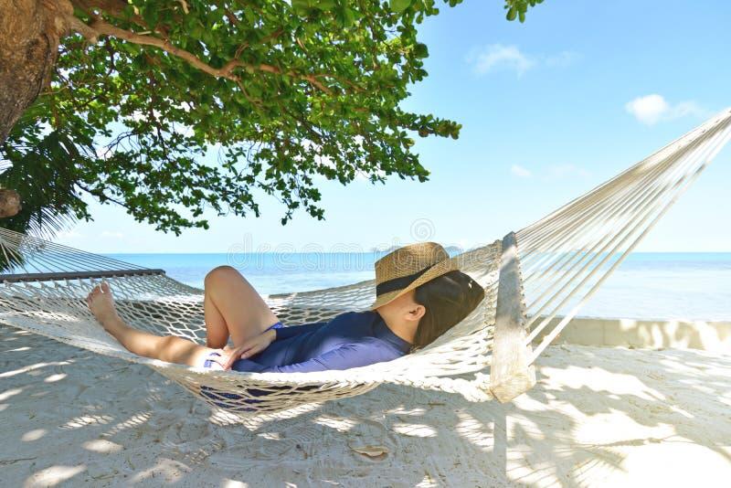 Lycklig kvinna i hängmatta på den tropiska stranden royaltyfri bild