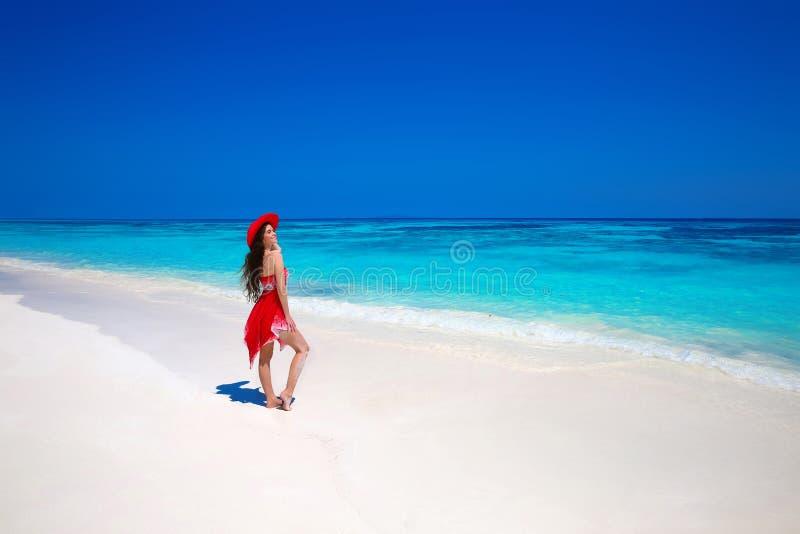 Lycklig kvinna i hatt som tycker om sommarsemester på den exotiska stranden i s royaltyfri bild