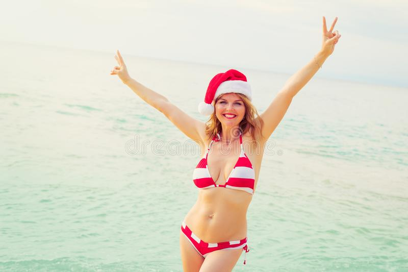 Lycklig kvinna i jultomtenhatt som tycker om vintersemester på stranden royaltyfria bilder