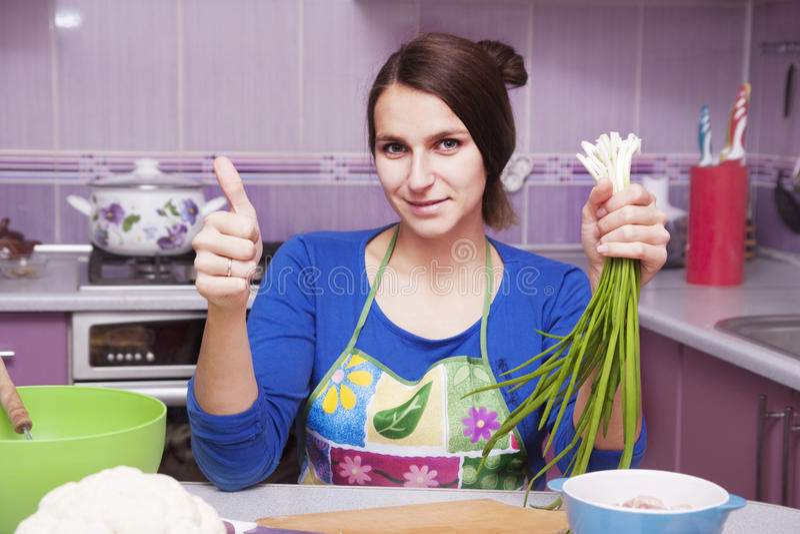 Lycklig kvinna i kök royaltyfri foto