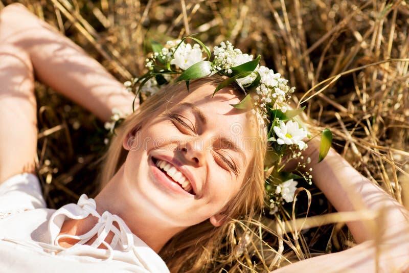 Lycklig kvinna i krans av blommor som ligger på sugrör arkivfoton