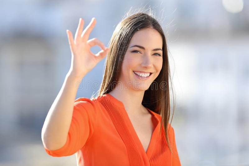 Lycklig kvinna i orange göra en gest ok tecken i en stad arkivbilder