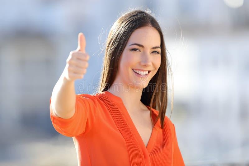Lycklig kvinna i orange göra en gest tumme upp i en stad royaltyfri foto