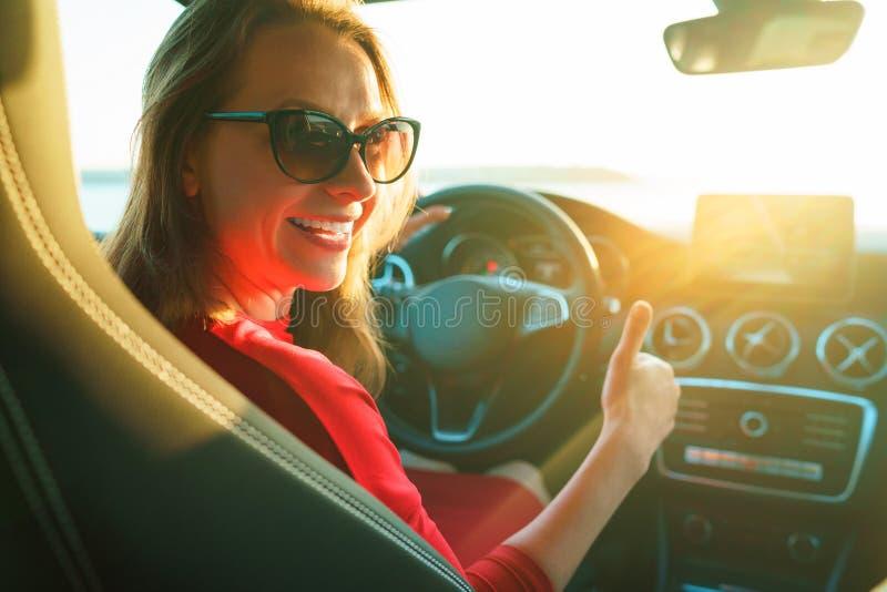 Lycklig kvinna i röd klänning med tummen upp sammanträde i bil arkivfoton