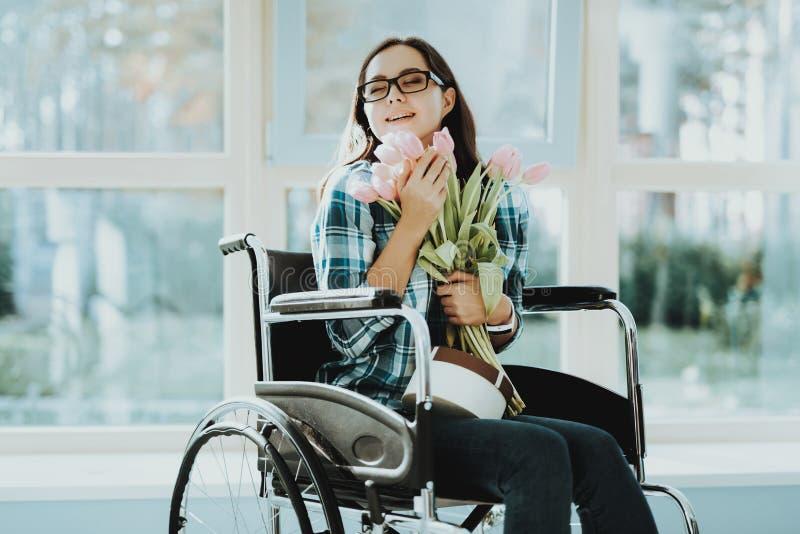 Lycklig kvinna i rullstol med blommor på flygplatsen royaltyfri fotografi