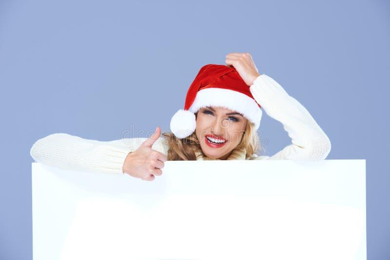 Lycklig kvinna i Santa Hat Behind Big Board fotografering för bildbyråer