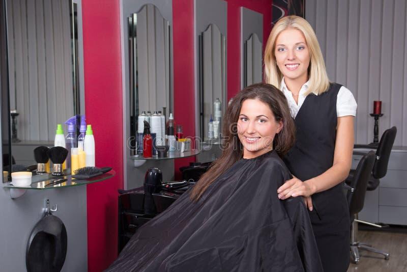 Lycklig kvinna i skönhetsalongen som får ett hårsnitt arkivbild