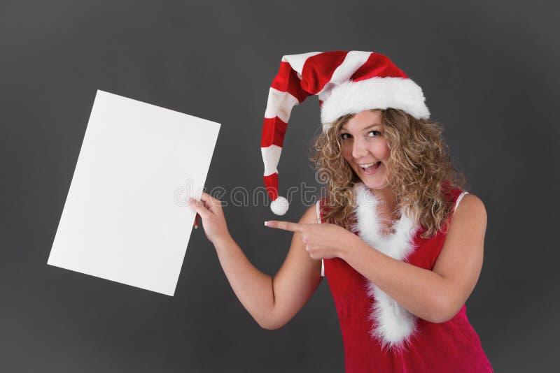 Lycklig kvinna i tecken för mellanrum för jultomtenhattinnehav arkivfoto