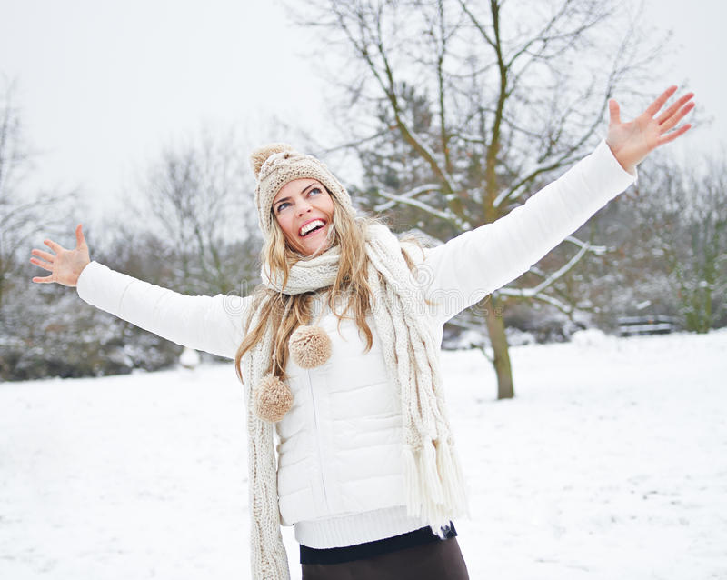 Lycklig kvinna i vinter med armar royaltyfria bilder