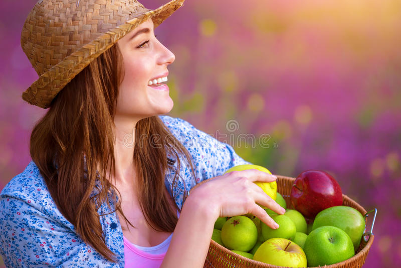 Lycklig kvinna med äpplekorgen royaltyfri fotografi