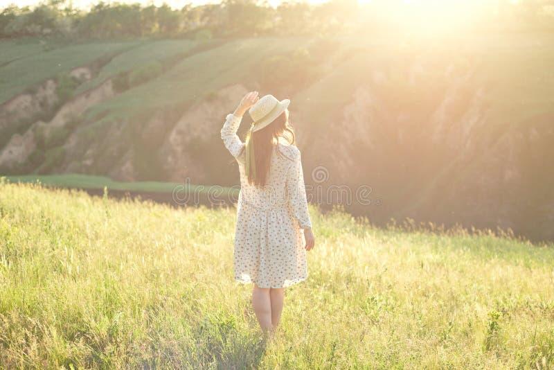 Lycklig kvinna med ?ppna armar att bli p? maximumet av bergklippkanten under solnedg?ngljushimmel som tycker om framg?ngen fotografering för bildbyråer