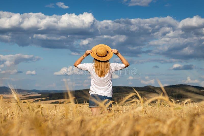 Lycklig kvinna med anseende för sugrörhatt i vetefält och tycka omsommar arkivbilder