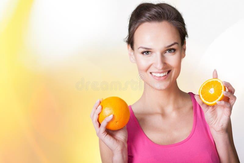 Lycklig kvinna med apelsiner royaltyfri bild
